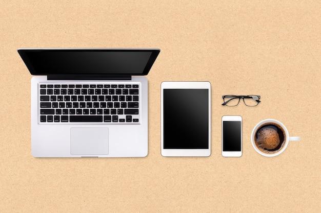 Laptop tabletsmartphone en koffie op bruine achtergrond met tekstruimte en exemplaarruimte
