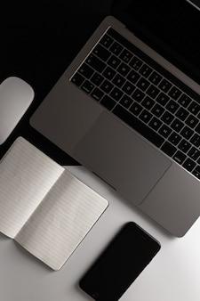 Laptop, telefoon en notitieboekje op het bureau