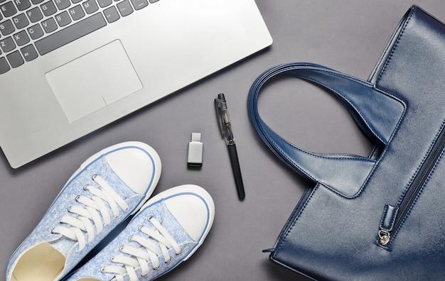 Laptop, usb stick en modieuze vrouwelijke accessoires op een grijze achtergrond: tas, portemonnee, sneakers, tas. bovenaanzicht plat liggen.