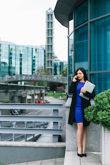 Laptop van de onderneemsterholding en het spreken op mobiele telefoon buiten de bureaubouw