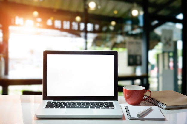 Laptop van het bureaumodel met blocnotedocument, pen en kop van koffie met het lege vertoningsscherm.