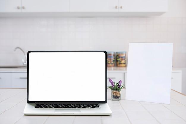 Laptop van het model lege scherm en leeg menuiskader op witte lijst in keukenruimte.