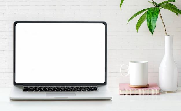 Laptop van het model lege scherm met kop, boek en houseplant op witte lijst en bakstenen muur.