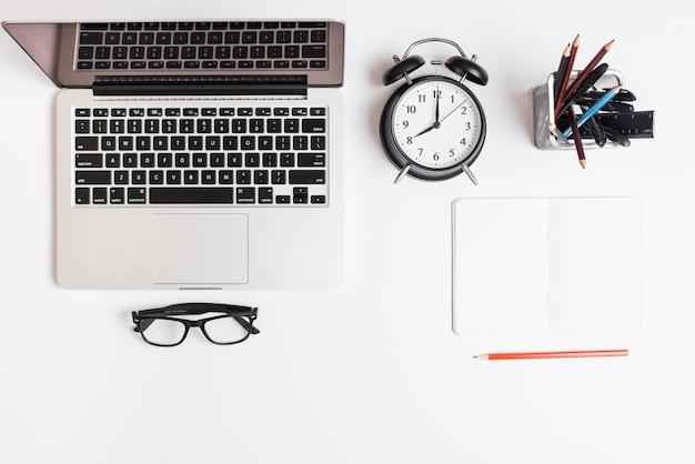 Laptop; wekker; bril; potlood en blocnote op witte achtergrond wordt geïsoleerd die