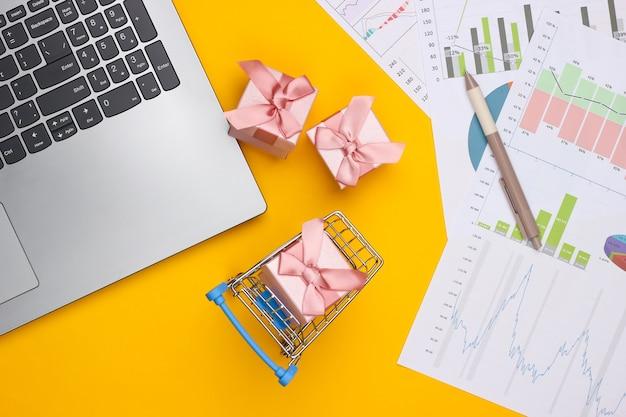 Laptop, winkelwagentje met geschenkdozen, grafieken en diagrammen op gele achtergrond. businessplan, financiële analyse, statistieken. bovenaanzicht