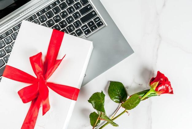 Laptop, witte geschenkdoos met rood lint en rose op witte marmeren tafel