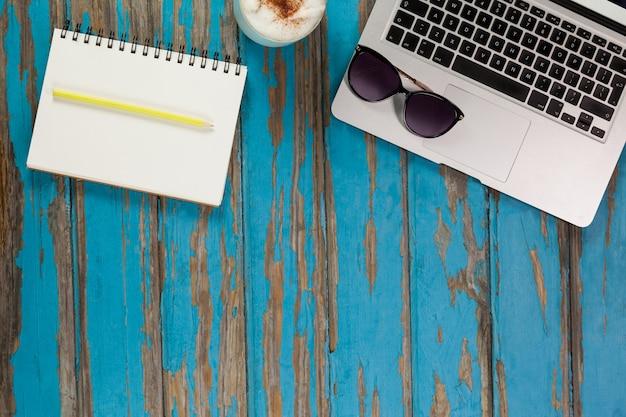 Laptop, zonnebril, koffiemok, notitieblok en potlood