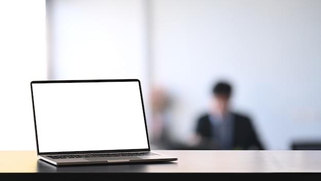 Laptopcomputer leeg scherm op zwarte tablet in vergaderruimte met kopie ruimte.