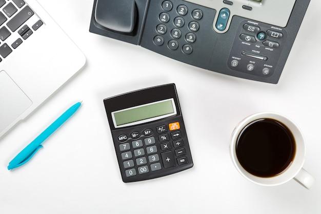 Laptopcomputer met kopje koffie, blauwe pen en moderne ip-telefoon en rekenmachine op witte ondergrond. t