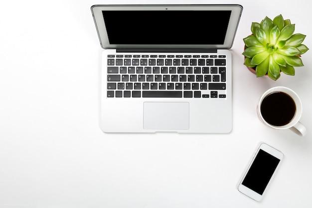 Laptopcomputer met plant in een pot, mobiele telefoon en kopje koffie op een witte ondergrond.