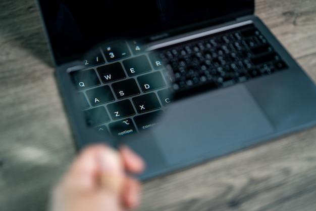 Laptopcomputer met vergrootglas op het laptop toetsenbordconcept van zoeken