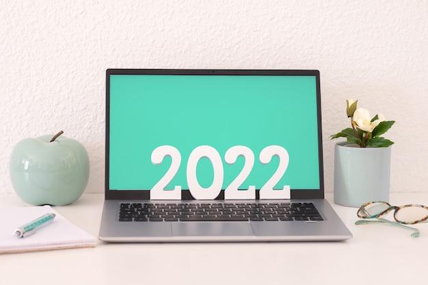 Laptopcomputer op witte achtergrond en groen scherm met 2022 nummer in houten figuren. zakelijk, werken op afstand, gelukkig nieuwjaar op bureau