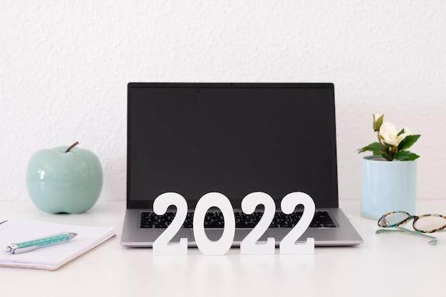 Laptopcomputer op witte achtergrond met 2022 nummer in houten figuren. zakelijk, werken op afstand, gelukkig nieuwjaar op bureau