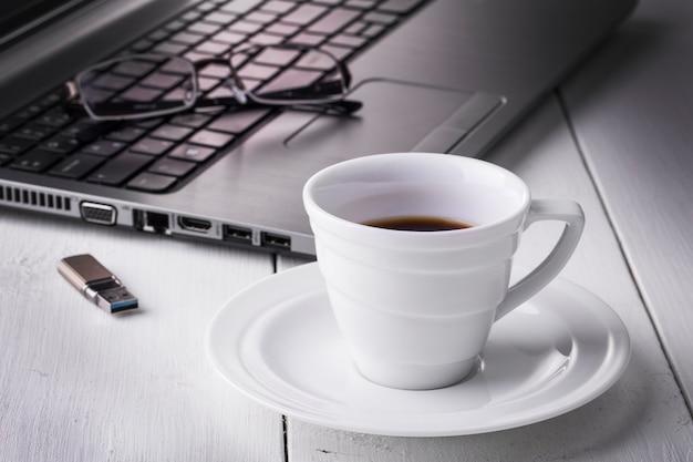 Laptopstick, bril en een kopje koffie op een witte houten tafel