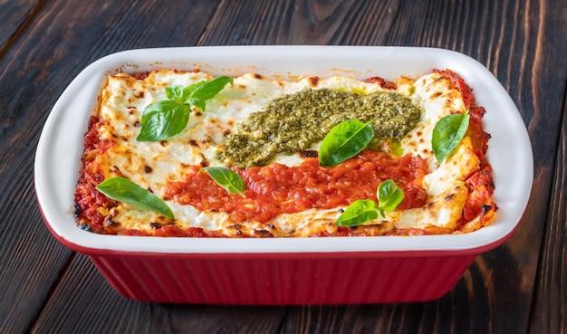 Lasagne gegarneerd met tomatensaus en pesto in bakvorm