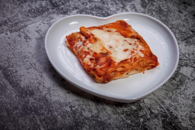 Lasagne met groenten op donkere gestructureerde achtergrond. traditionele voedselgezondheid in witte plaat in vormhart met lasagne met groenten. heerlijk gezond voedseldieet. ruimte kopiëren