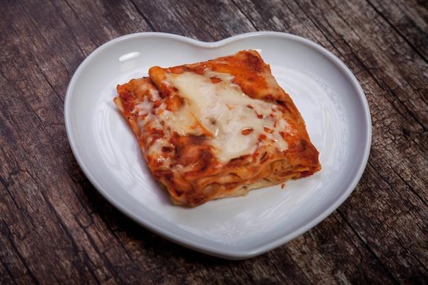 Lasagne met groenten op donkere houten ondergrond. traditionele voedselgezondheid in witte plaat in vormhart met lasagne met groenten. heerlijk gezond voedseldieet. ruimte kopiëren