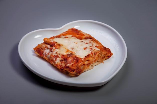 Lasagne met groenten op donkergrijze kleur achtergrond. traditionele voedselgezondheid in witte plaat in vormhart met lasagne met groenten. heerlijk gezond voedseldieet. ruimte kopiëren