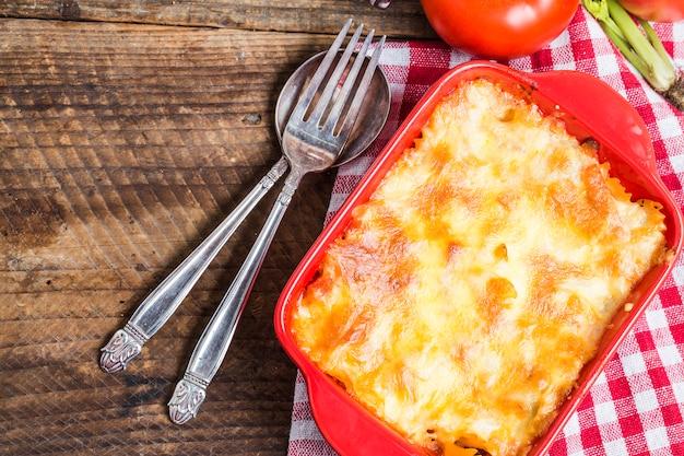 Lasagne naast een vork en lepel