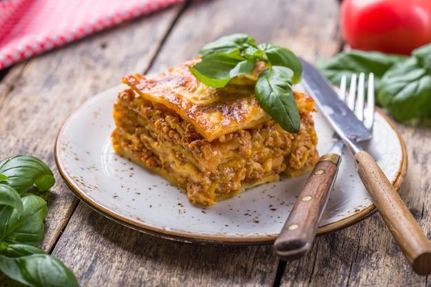 Lasagne van vlees met verse basilicum en parmezaanse kaas in een plaat op houten tafel.