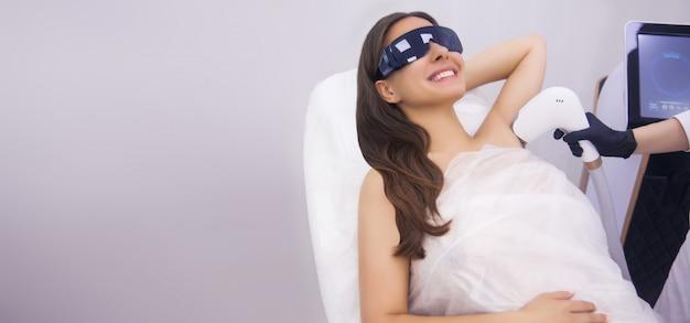 Laser epileren en cosmetologie in schoonheidssalon. haarverwijderingsprocedure. laser epileren, cosmetologie, spa, ontharing concept. mooie donkerbruine vrouw die haar krijgt die op underarm verwijdert.