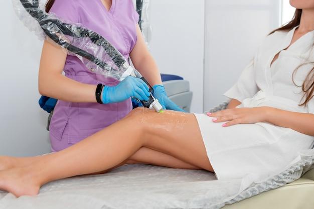Laser epileren op mooie vrouwelijke benen bij schoonheidskliniek