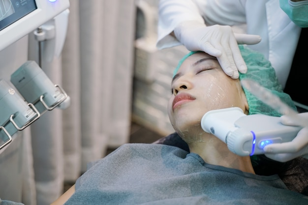 Laser of frequentie huidverstrakking face lift behandelingsprocedure omvat. jonge vrouw die laser kin krijgt.