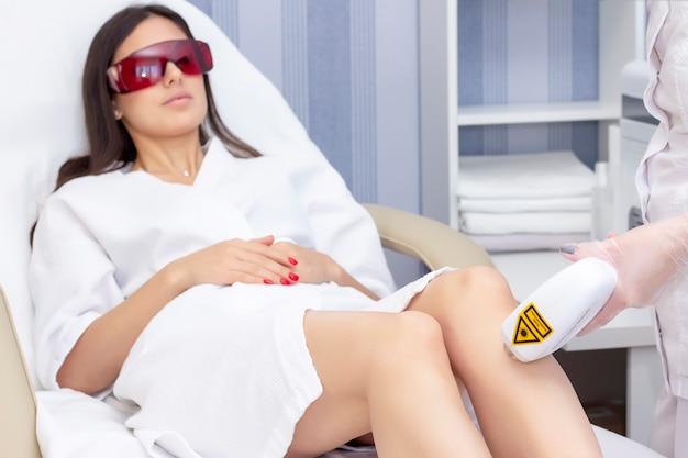 Laser ontharing benen. laserepilatie en cosmetologie. cosmetische procedure voor ontharing. laserepilatie en cosmetologie. cosmetologie en spa concept