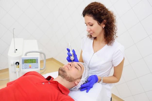 Lasercosmetologie. de arts verwijdert pigmentvlekken of wratten neodymiumlaserpatiënten.