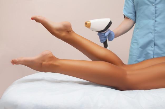 Laserepilatie en cosmetologie in schoonheidssalon. ontharingsprocedure. concept van laserepilatie, cosmetologie, spa en ontharing. mooie vrouw die haar krijgt dat op benen verwijdert
