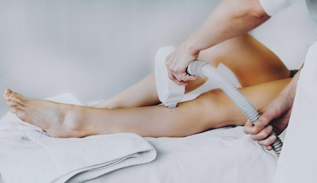 Laserepilatieprocedure op de benen van de cliënt gedaan in de spa-salon