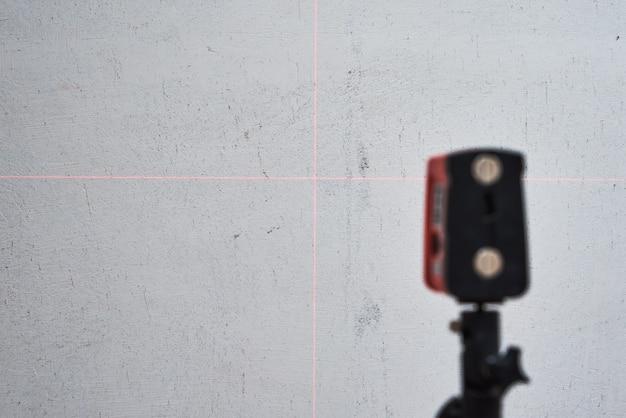 Laserniveau controleren muur, close-up. renovatie concept