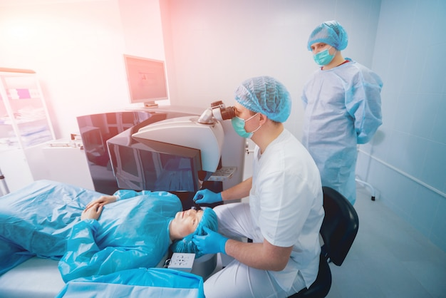Laserzichtcorrectie. een patiënt en een team van chirurgen in de operatiekamer tijdens oogheelkundige chirurgie. ooglid speculum. lasik-behandeling.