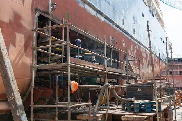 Lasser die aan schip werkt dat werf herstelt - het hete werk