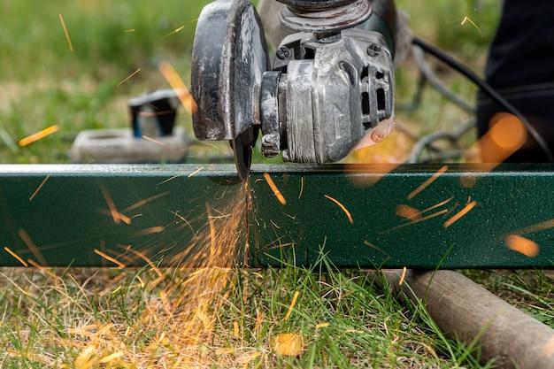 Lasser die een metalen slijper gebruikt om een metaal op het gras in het dorp te snijden, felle flitsen