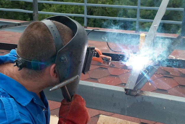 Lasser in de fabriek die met metalen constructie werkt