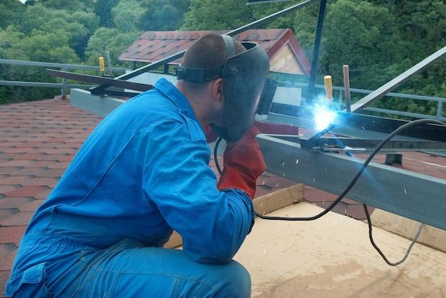 Lasser in de fabriek die met metalen constructie werkt Premium Foto