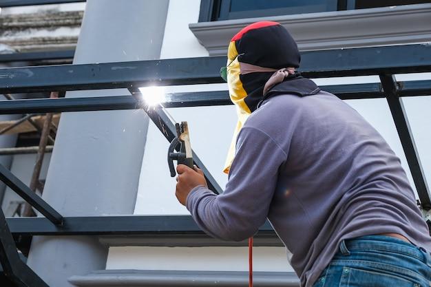 Lasser is de stalen constructie aan het lassen om aan het huis toe te voegen.