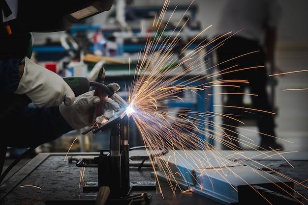 Lasser last de metalen onderdelen in de auto-assemblagefabriek en oefent de vaardigheden van de lasser in industriële fabrieken.