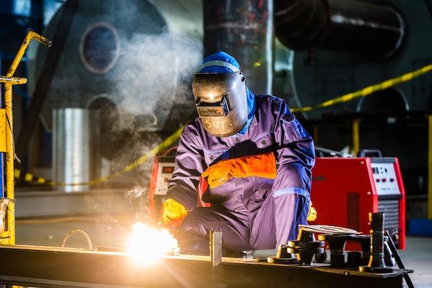Lasser werkzaam in een industriële omgeving die stalen apparatuur vervaardigt