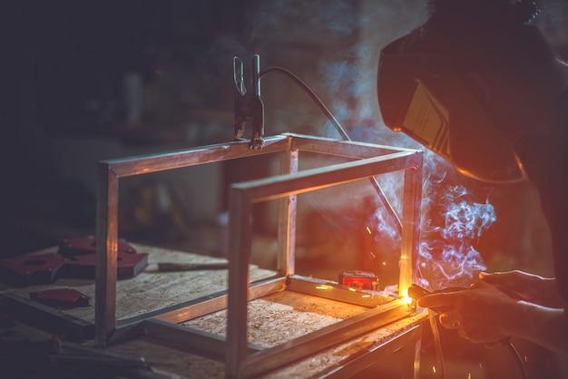 Lassers die gemaakt metaal bewerken. / lassers die in de fabriek met constructie werken.