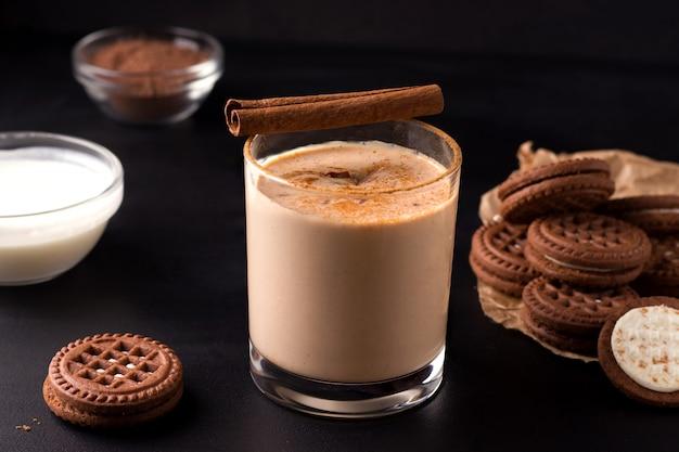 Lassi chocoladedrank op een zwarte achtergrond naast de ingrediënten van yoghurt en cacao