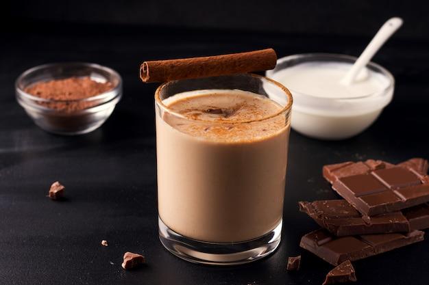 Lassi chocoladedrank op een zwarte achtergrond naast de ingrediënten yoghurt, cacao en chocolade
