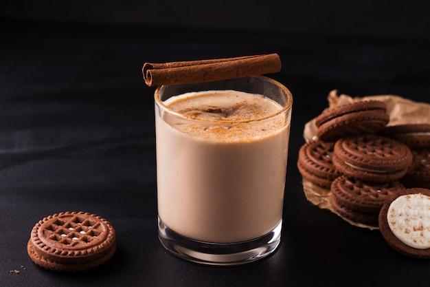 Lassi indiase chocoladedrank naast koekjes op zwarte achtergrond