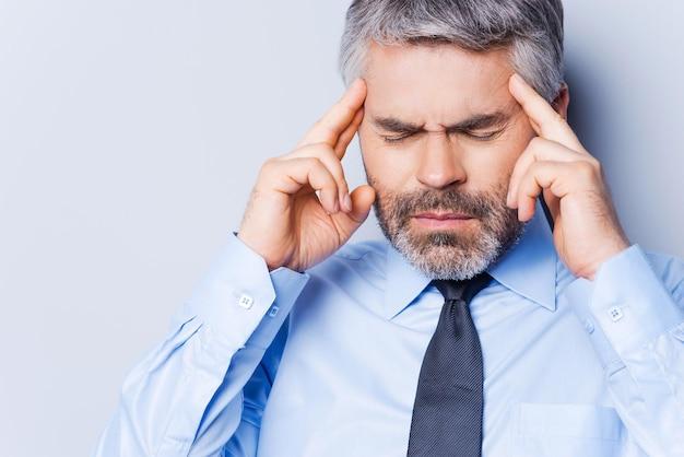 Last van hoofdpijn. depressieve volwassen man in overhemd en stropdas die het hoofd met de vingers aanraakt en de ogen gesloten houdt terwijl hij tegen een grijze achtergrond staat