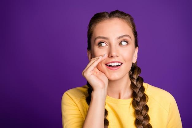 Lastig dame lange vlechten kapsel vasthouden arm dichtbij mond delen vers roddels babbelaar persoon slijtage casual geel pullover geïsoleerde paarse kleur muur