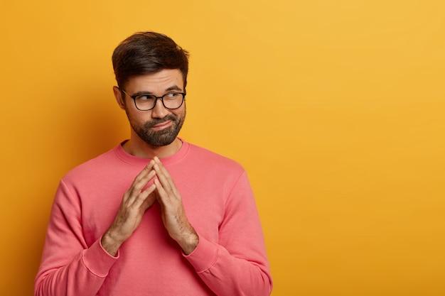 Lastige, bedachtzame, bebaarde man steekt vingers, heeft een of andere bedoeling in gedachten, overweegt plannen voor de toekomst, kijkt mysterieus opzij, heeft een plan, draagt een roze trui, geïsoleerd over gele muur