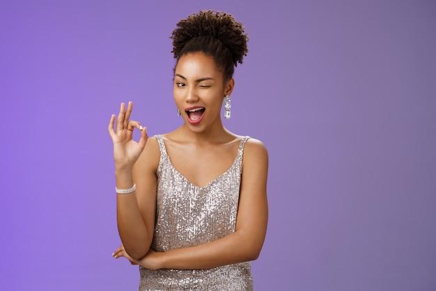 Lastige betrouwbare knappe charmante jonge afro-amerikaanse vriendin beloven geheim houden knipogen bevestigingsgebaar toon oké ok bevestigend teken snap je, heb een sluw plan, blauwe achtergrond.