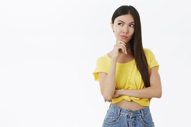 Lastige en slimme creatieve jonge stijlvolle vrouw in gele vriendin die van plan is om wraak te nemen terwijl ze nadenkend wenkbrauw opheft