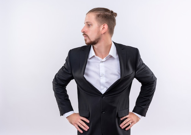 Lastige knappe zakenman gekleed pak opzij kijken staande op witte achtergrond